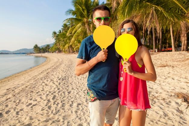 Junges schönes paar in der liebe, die tischtennis am tropischen strand spielt, spaß, sommerferien, aktiv, lächelnd, lustig, positiv hat