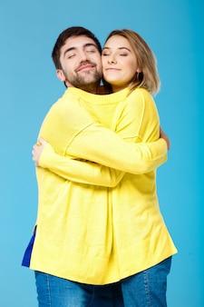 Junges schönes paar in einem gelben pullover, der über blaue wand umarmt
