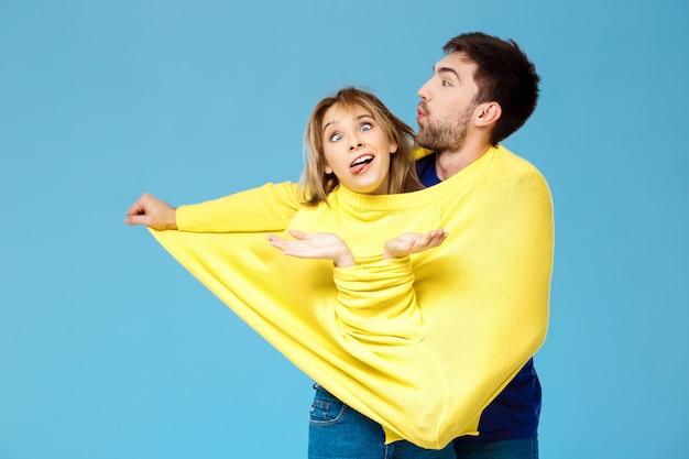 Junges schönes paar in einem gelben pullover posierend lächelnd, der spaß über blauer wand hat