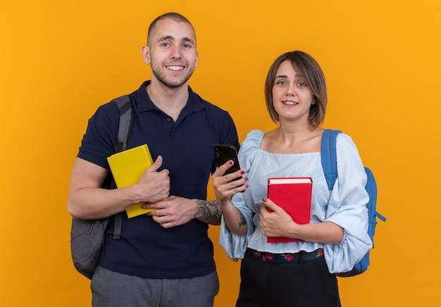 Junges schönes paar in freizeitkleidung mit rucksäcken, die bücher und smartphone halten und fröhlich glücklich und positives ansehen lächeln