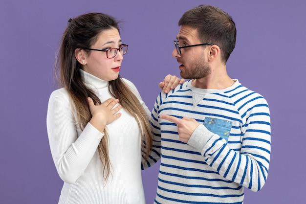 Junges schönes paar in lässiger kleidung verwirrter mann, der mit zeigefinger auf seine überraschte freundin zeigt, die valentinstag feiert, der über lila wand steht