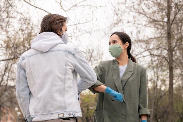 Junges schönes paar in schutzmasken, die sich mit ellbogenberührungsgeste im park grüßen