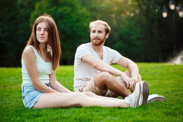 Junges schönes paar lächelnd, auf gras im park sitzend.