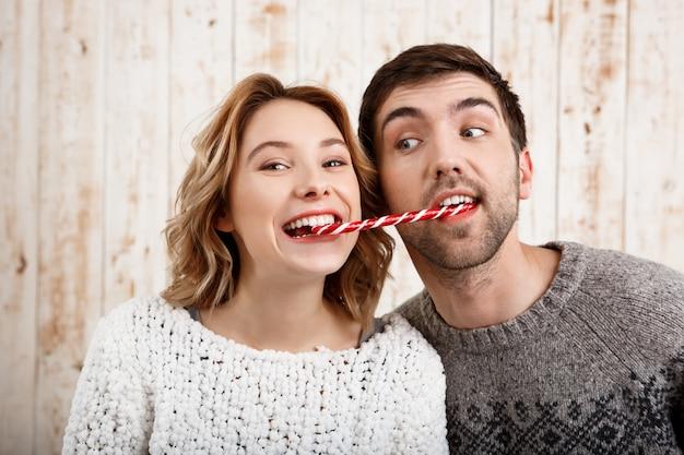 Junges schönes paar lächelnd, das weihnachtsbonbon über holzwand isst