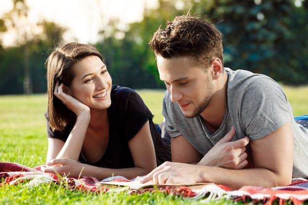 Junges schönes paar lächelnd, lesend, im park ruhend