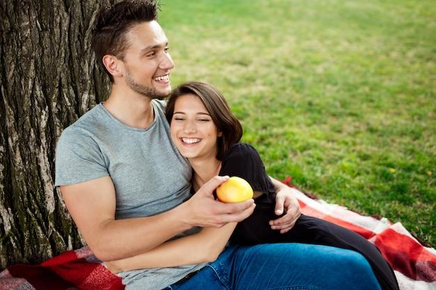 Junges schönes paar lächelnd, ruhend auf picknick im park.