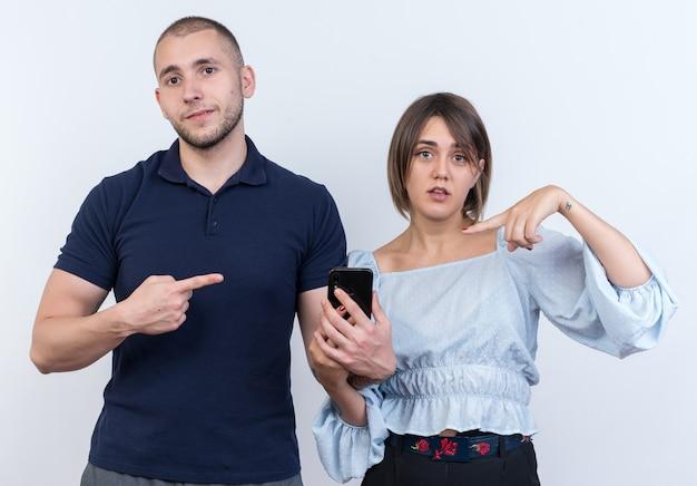 Junges schönes paar, mann und frau, die einen mann mit smartphone suchen, der mit dem zeigefinger auf seine verwirrte freundin zeigt