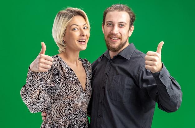 Junges schönes paar mann und frau, die kamera glücklich und fröhlich lächelnd breit zeigt, zeigt daumen hoch, den valentinstag zu feiern, der über grünem hintergrund steht