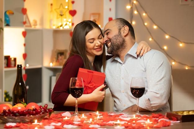 Junges schönes paar mann und frau mit geschenk, das am tisch sitzt, verziert mit kerzen und rosenblättern glücklich in der liebe, die internationalen frauentag im dekorierten wohnzimmer feiert