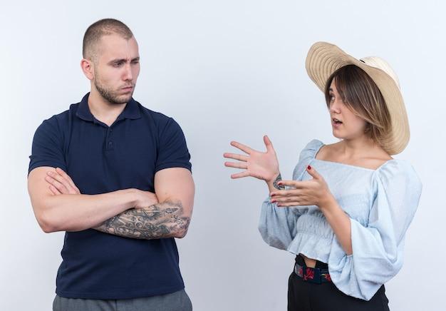 Junges schönes paar mann und frau streiten verwirrte frau, die ihren beleidigten freund ansieht, der steht