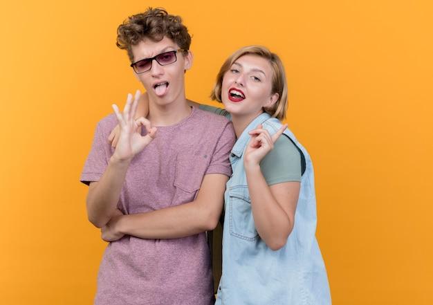 Junges schönes paar mann und frau tragen freizeitkleidung posierend und lächelnd zeigt ok zeichen, das über orange wand steht