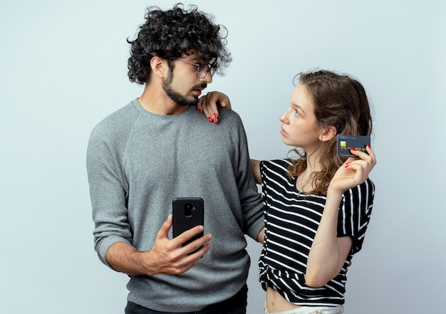 Junges schönes paar mann und frauen, verwirrter mann, der smartphone hält und ihre freundin betrachtet, die seine kreditkarte über weißem hintergrund hält