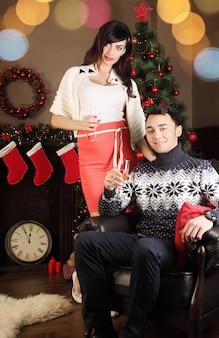 Junges schönes paar mit gläsern champagner zu weihnachten, dunkles interieur