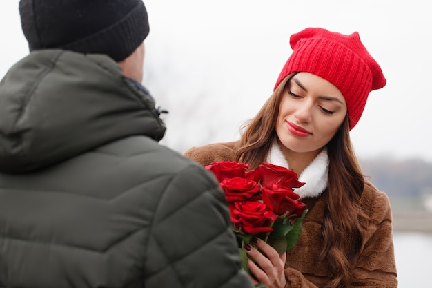Junges schönes paar mit roten rosen im freien