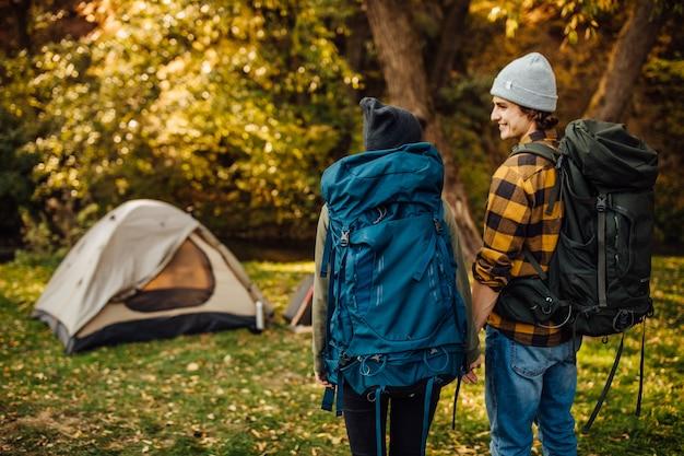 Junges schönes paar mit wanderrucksäcken geht trekking