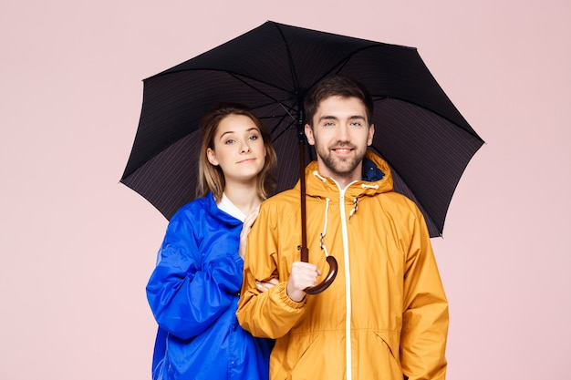 Junges schönes paar posiert in regenmänteln, die regenschirm über hellrosa wand halten