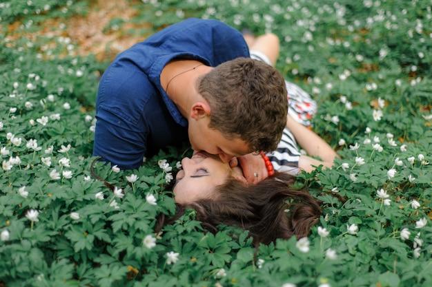 Junges schönes paar verliebt in den wald. ein mann und eine frau liegen und umarmen sich in frühlingswaldfarben. einen moment vor dem kuss. nahansicht. freiraum.