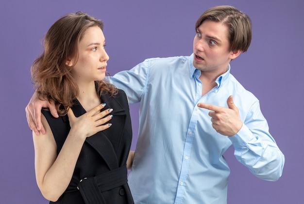 Junges schönes paar verwirrter mann, der mit zeigefinger auf seine überraschte freundin valentinstagkonzept zeigt, das über blauer wand steht