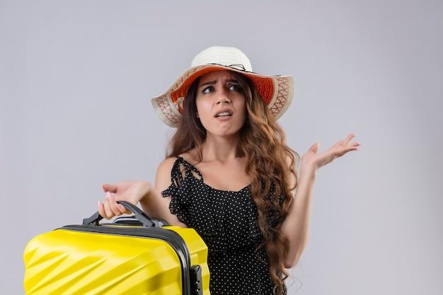 Junges schönes reisendes mädchen im kleid im tupfen im sommerhut, der koffer ahnungslos hält und verwirrt hat, keine antwort stehend mit armen zu haben, die über weißem hintergrund erhoben werden