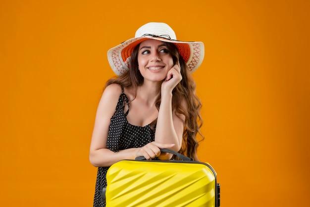 Junges schönes reisendes mädchen im kleid im tupfen im sommerhut stehend mit koffer, der fröhlich mit glücklichem gesicht über gelbem hintergrund lächelt