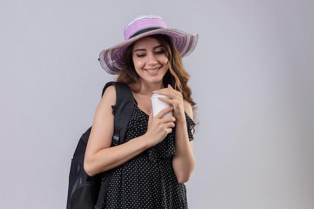 Junges schönes reisendes mädchen im sommerhut mit rucksack, der kaffeetasse hält, die fröhlich glücklich und positiv steht über weißem hintergrund