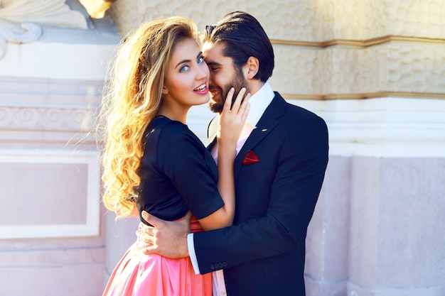 Junges schönes sexy paar umarmt sich auf der straße, genießt ihr romantisches date, verbringt eine schöne zeit zusammen und posiert auf der straße bei klassischen, glamourösen, trendigen abendkleidern. helle sonnige farben.