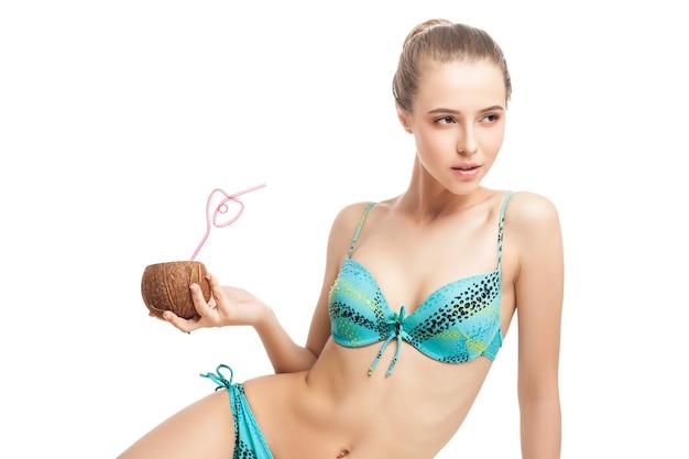 Junges schönes sommermädchen, das frische kokosnuss mit einem strohhalm hält