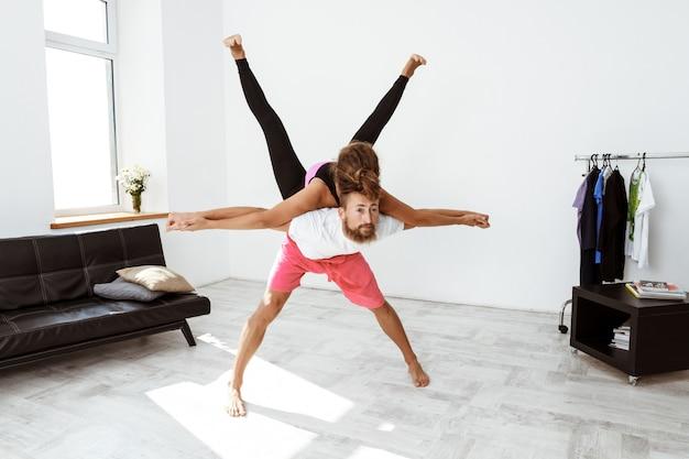 Junges schönes sportliches paar, das partner yoga asanas zu hause praktiziert.