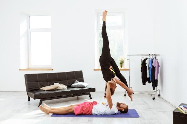 Junges schönes sportliches paar, das yoga-asanas zu hause praktiziert.