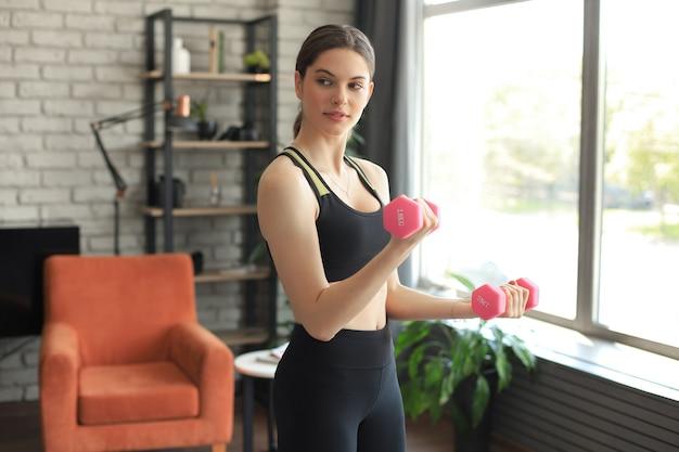 Junges schönes sportmädchen in leggings und einem oberteil macht übungen mit hanteln. gesunder lebensstil. eine frau treibt zu hause sport.