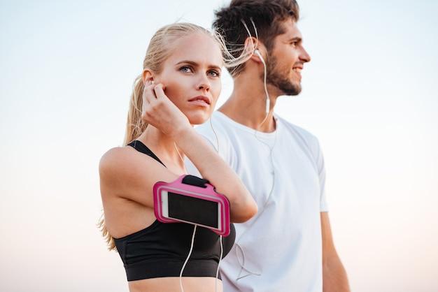 Junges schönes sportpaar, das sich auf einen marathon vorbereitet