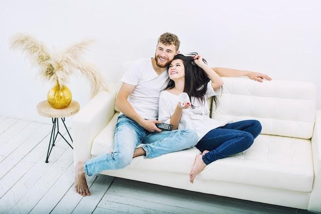 Junges schönes und glückliches paar mann und frau zu hause auf weißem sofa beim fernsehen lächelnd und umarmend