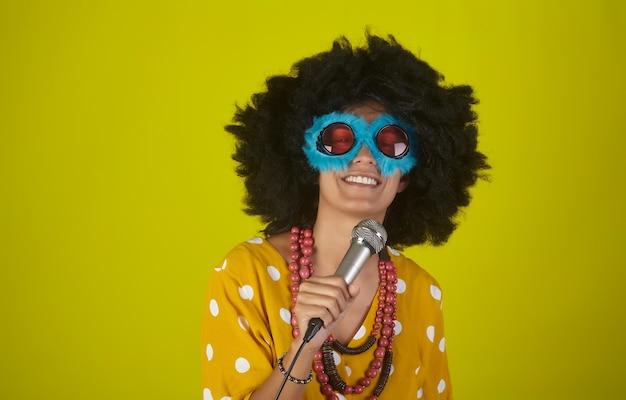Junges schönes und lächelndes mädchen mit gelockter afro-frisur und lustigen brillen, die mit mikrofon über gelber wand singen