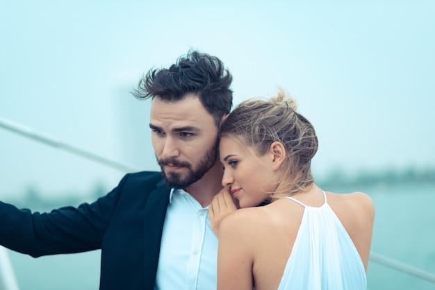 Junges schönes verheiratetes paar, das im urlaub auf der yacht umfasst