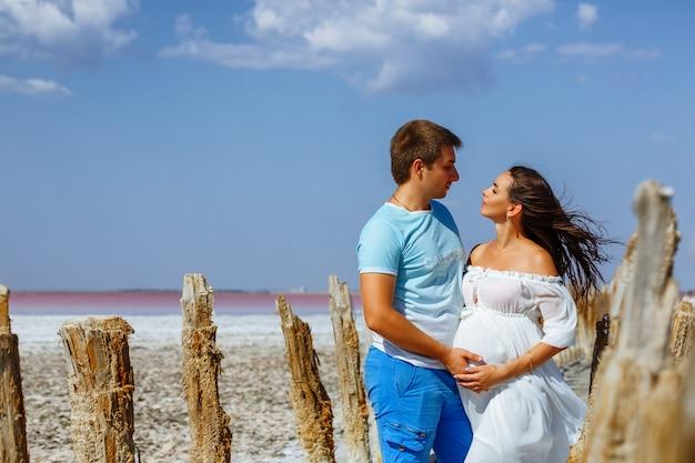 Junges schönes verheiratetes paar, schwangere frau im weißen kleid in der natur
