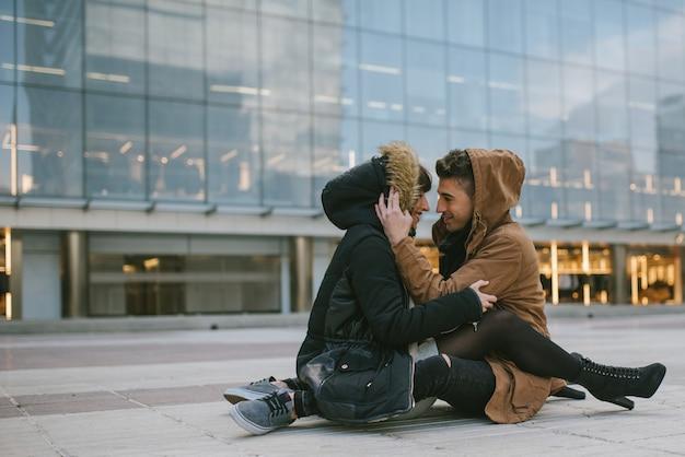 Junges schönes verliebtes paar, das sich auf romantische weise mitten auf der straße umarmt