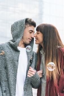 Junges schönes verliebtes paar, das sich mitten auf der straße auf romantische weise mit seifenblasen umarmt