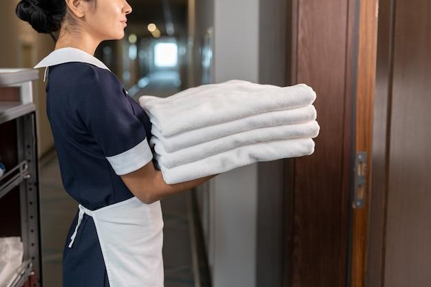 Junges schönes zimmermädchen in uniform, das einen stapel sauberer gefalteter handtücher hält, während sie eines der hotelzimmer betritt und sie den gästen gibt