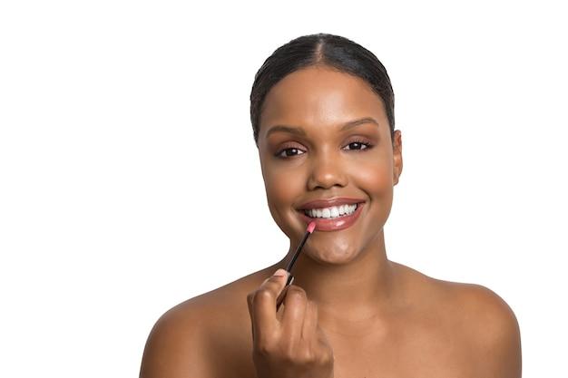 Junges schönheitsmodell mit makelloser und glatter haut lächelt beim auftragen von lippenstift auf eine weiße wand