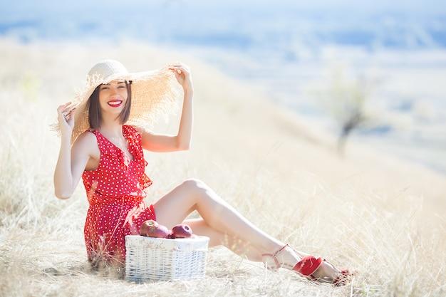 Junges schönheitsporträt draußen auf saftigem sommer oder herbst frau auf abfallzeit. dame auf der natur, die rotes stilvolles kleid trägt.