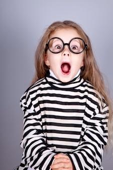 Junges schreiendes kind in den gläsern und in gestreifter gestrickter jacke.