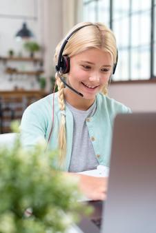 Junges schülermädchen, das auf laptop lernt