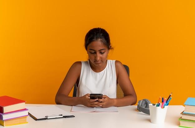 Junges schulmädchen, das am schreibtisch mit schulwerkzeugwählnummer am telefon lokalisiert auf orange wand sitzt
