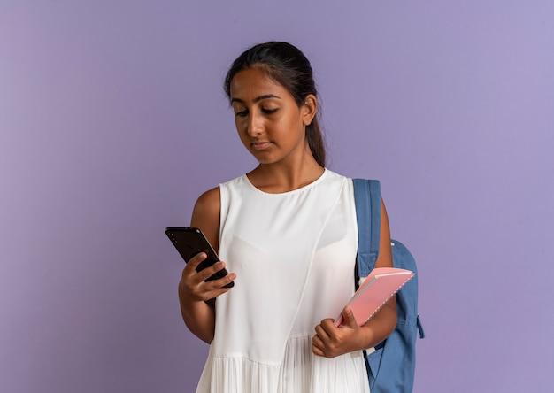 Junges schulmädchen, das rückentasche hält, das notizbuch hält und telefon in ihrer hand auf lila betrachtet