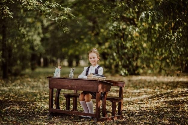 Junges schulmädchen in der uniform, die auf einem hölzernen schreibtisch in einem park sitzt