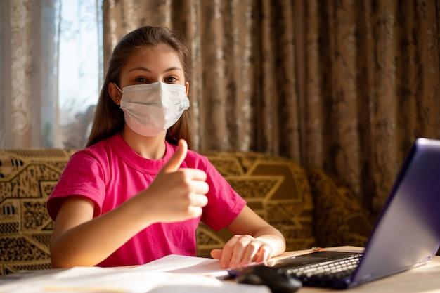 Junges schulmädchen in medizinischer maske zeigt daumen hoch, glücklich, unterricht zu hause zu haben, fernunterricht zu haben und nicht zur schule zu gehen. konzept des lebens während der coronavirus-quarantäne