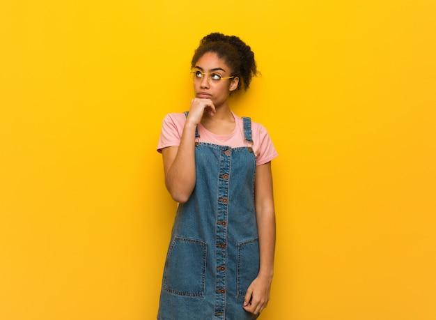 Junges schwarzafrikanermädchen mit blauen augen denkend an eine idee