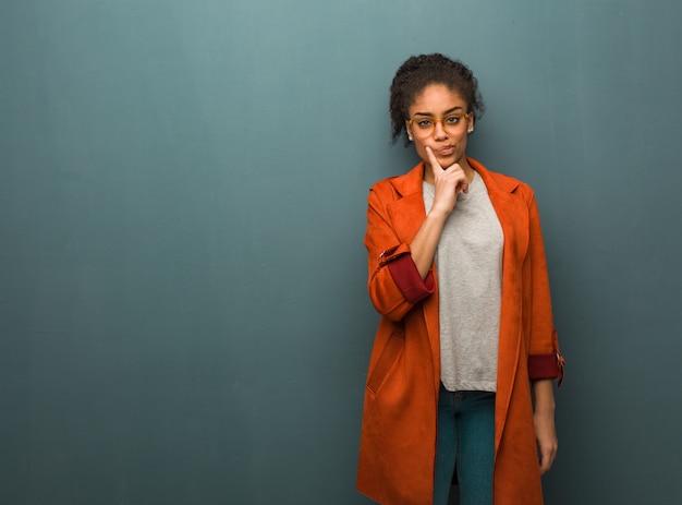 Junges schwarzafrikanermädchen mit blauen augen zweifelnd und verwirrt