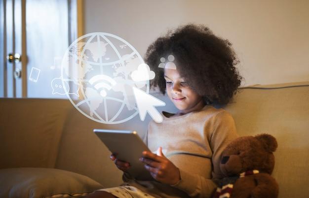 Junges schwarzes mädchen, das eine digitale tablette verwendet