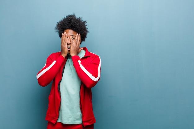 Junges schwarzes sportmann-bedeckungsgesicht mit den händen, spähend zwischen finger mit überraschtem ausdruck und schauen zur seite gegen schmutzwand
